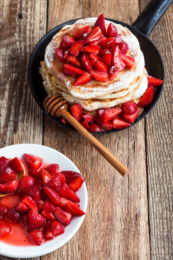 Strawberry  pancakes,  summer brunch rural table. Brunch, favorite morning meal. Homemade berry  pancakes, fresh summer dessert with strawberries, honey and stock photography
