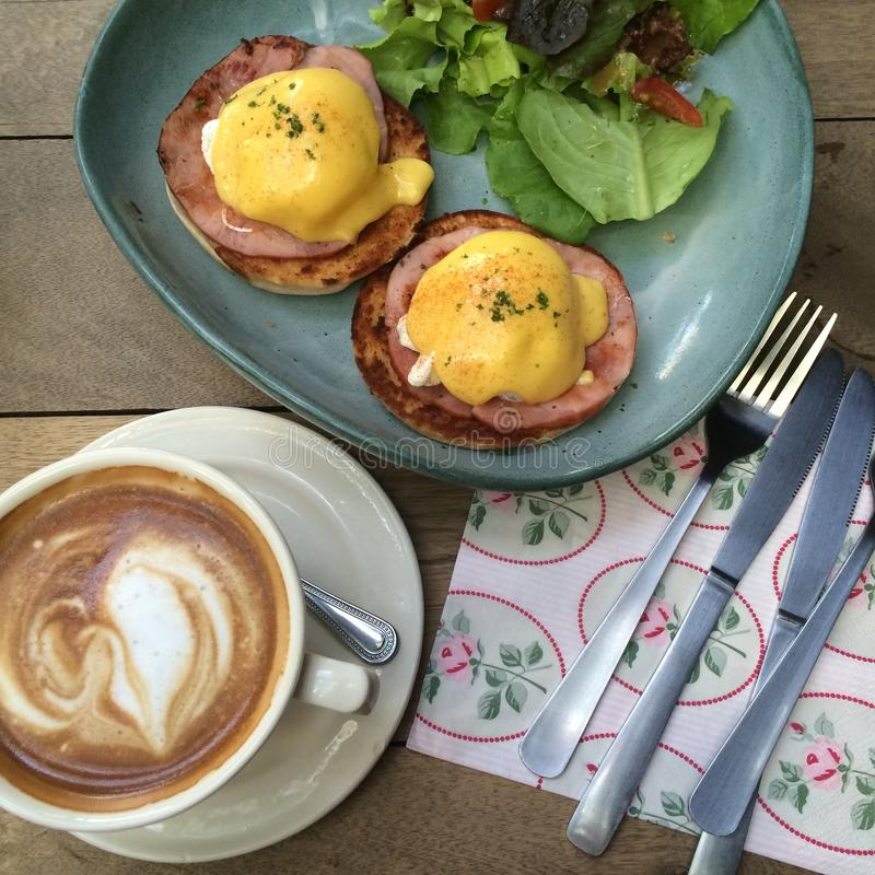 Brunch. Happy meal with egg Benedict and hot latte for brunch royalty free stock images