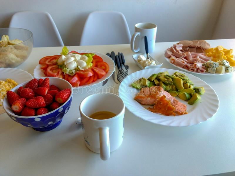 Brunch time: healthy and tasty food. A healthy brunch of salmon, cheese, tomato, strawberries and coffee fish bread food epicure smoked breakfast snack canape royalty free stock photography