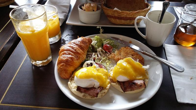 Brunch. Very enjoyable brunch with benedict eggs , croissant, patties, orange juice, english muffin, bacon, salad stock photo