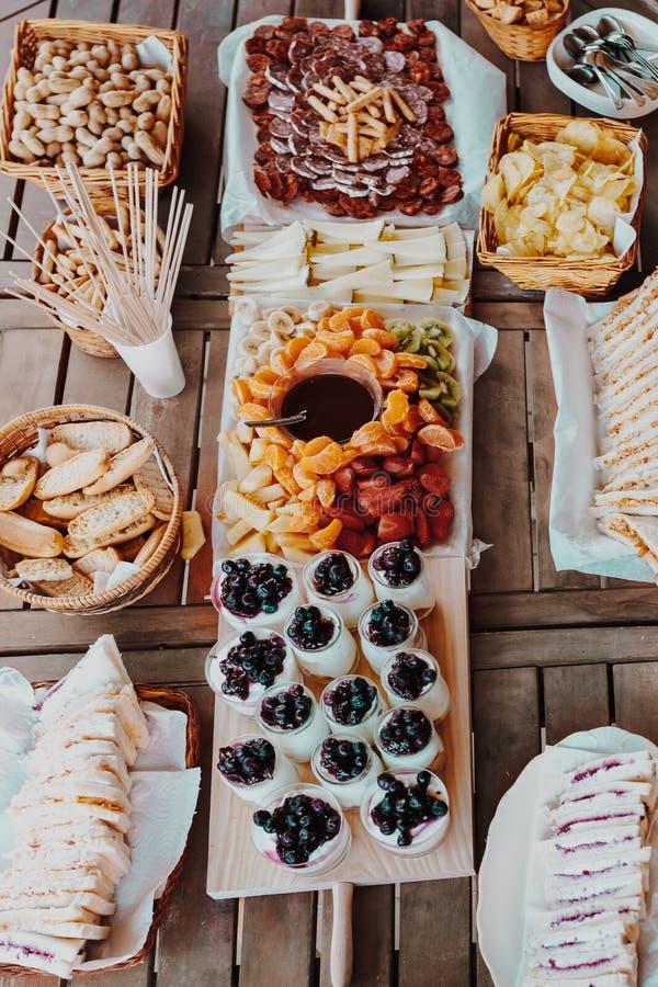 brunching 开胃菜桌用乳酪,芯片,面包,三明治,酸奶,果子巧克力涮制菜肴蜜桔,香蕉,猕猴桃, 免版税图库摄影