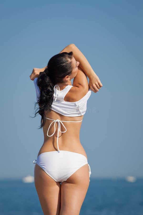 Brune attrayante dans les vêtements de bain blancs se déshabillant sur la plage photographie stock