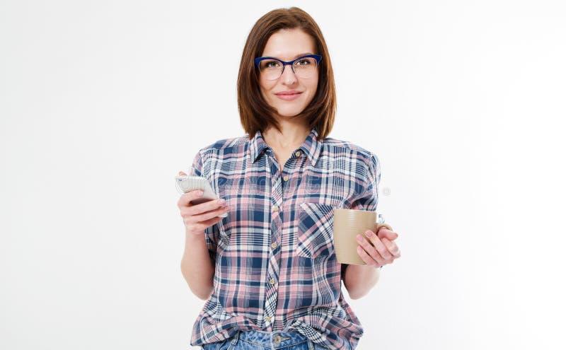 Brune attrayante en verres avec la tasse de café et de téléphones d'isolement sur le fond blanc, femme moderne image libre de droits