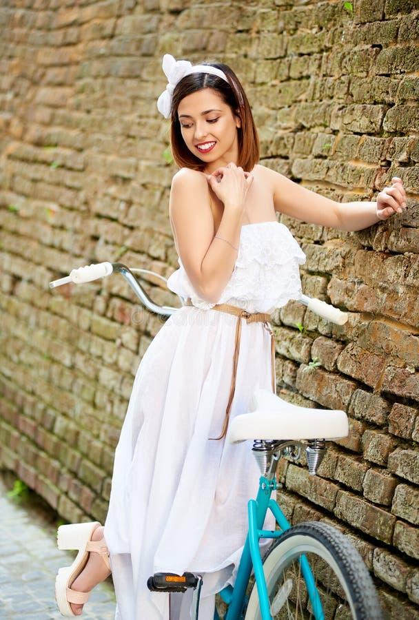 Brune attrayante posant avec le vélo bleu près du vieux mur de briques photos stock