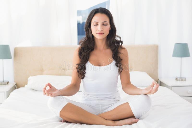 Brune calme faisant le yoga sur le lit photographie stock
