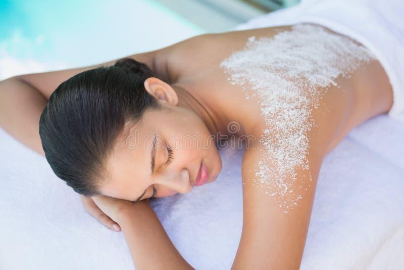 Brune calme se trouvant sur la serviette avec le dos de traitement de sel dessus photo libre de droits