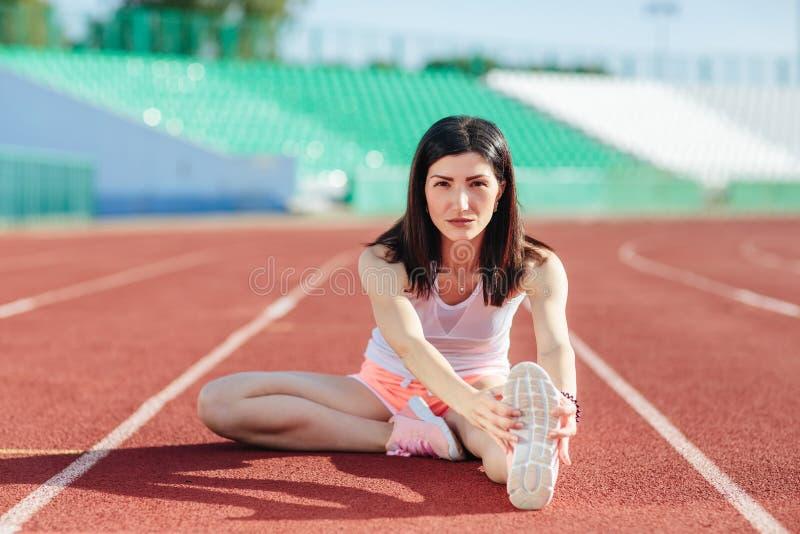 Brune d'athlète de jeune femme dans des shorts et des dessus de réservoir roses sur le mode de vie sportif de stade se reposant s photo libre de droits