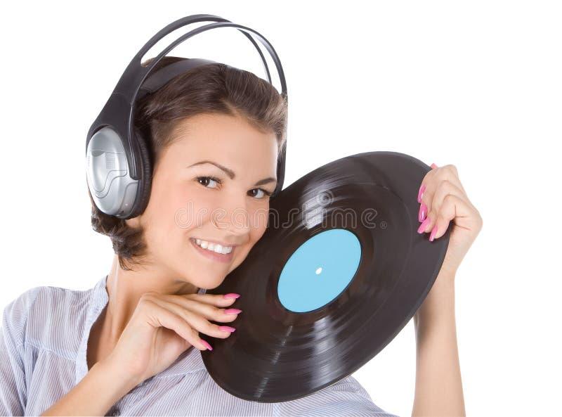 brune dans des écouteurs avec le disque vinyle au-dessus du blanc images libres de droits