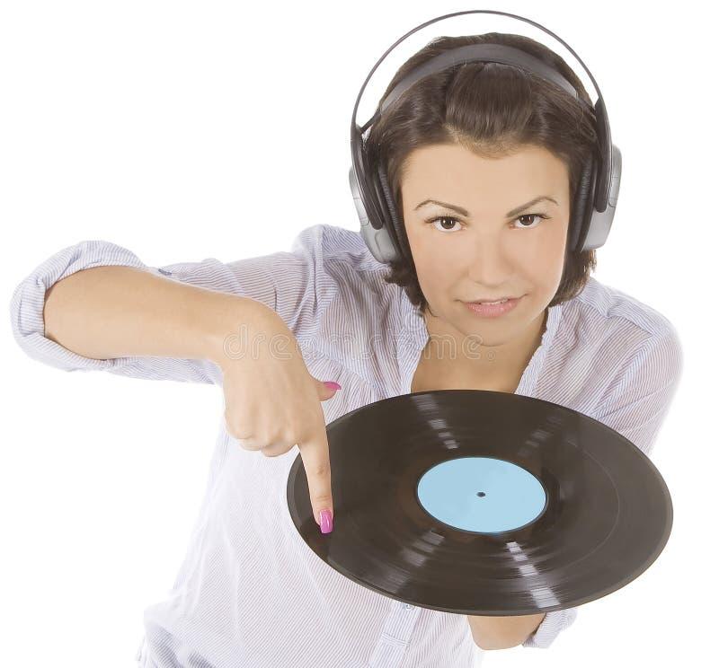brune dans des écouteurs avec le disque vinyle au-dessus du blanc image libre de droits