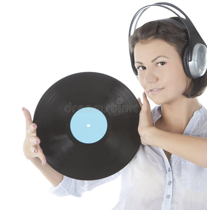 brune dans des écouteurs avec le disque vinyle au-dessus du blanc photos stock