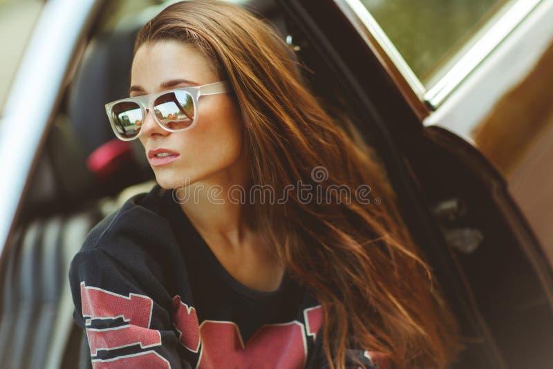 Brune dans des lunettes de soleil se reposant dans la voiture, photo teintée photos stock