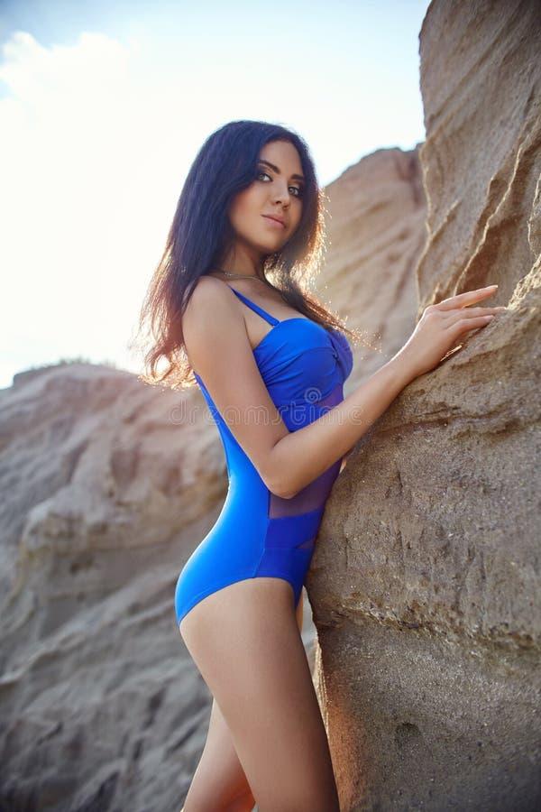 Brune dans le maillot de bain sur une plage sablonneuse dans le soleil de soirée E image stock