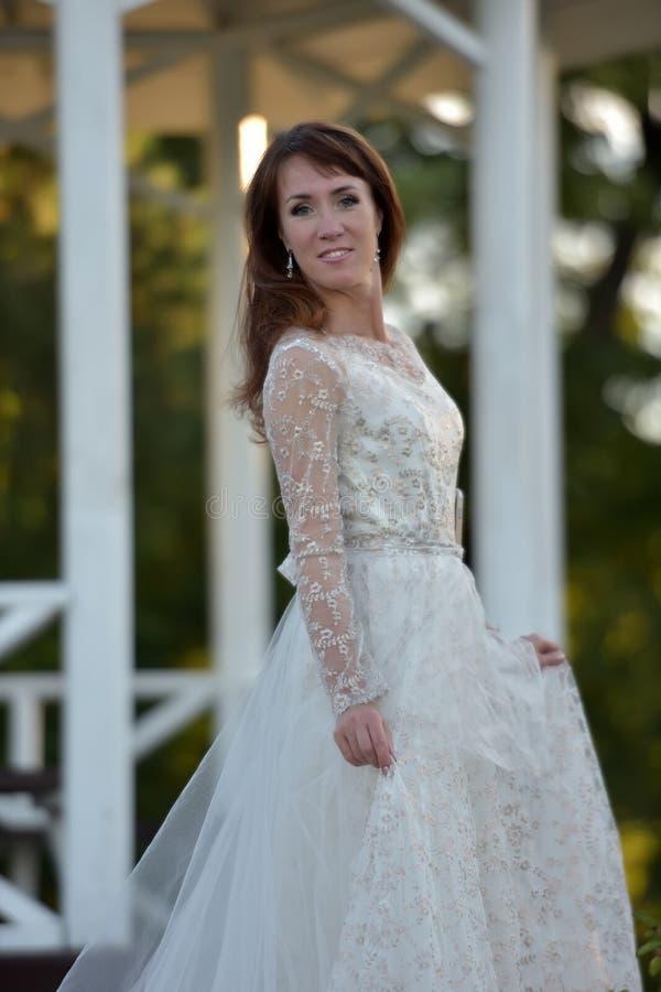 Brune dans une robe blanche en parc image stock