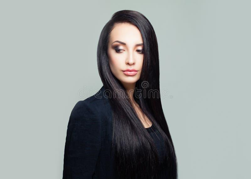 Brune de femme élégante sur le fond gris, portrait photos stock