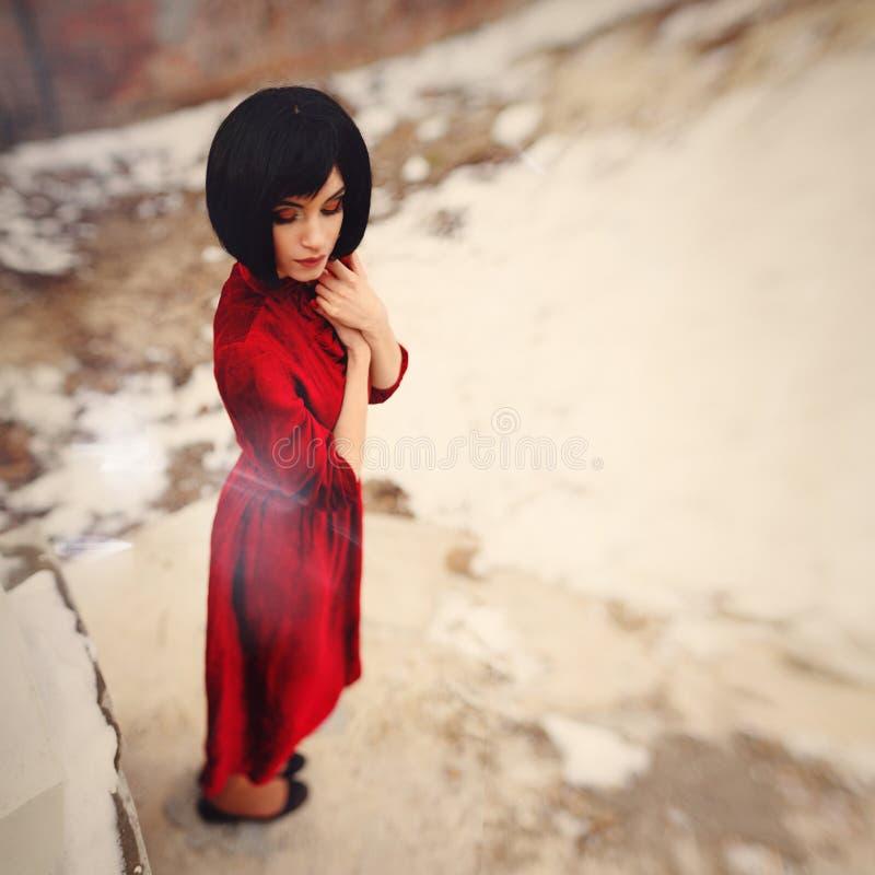 Brune de fille avec les cheveux courts dans la robe rouge de vintage photo stock