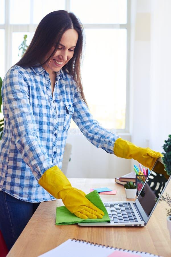 Brune de sourire dans la chemise et gants époussetant l'ordinateur portable photo stock