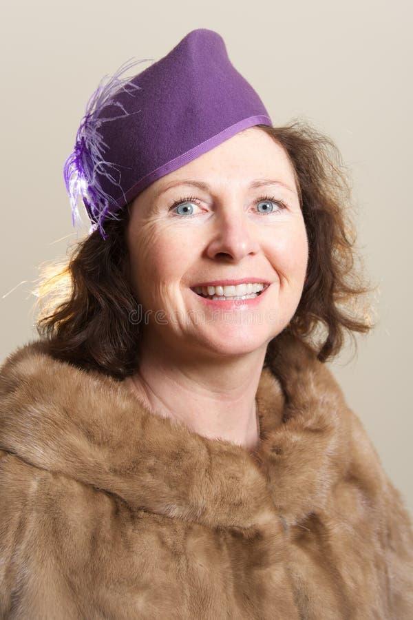 Brune de sourire en chapeau et fourrure pourpres photo libre de droits