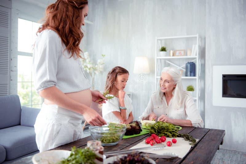 Brune enceinte faisant cuire le dîner avec la maman et la fille images stock