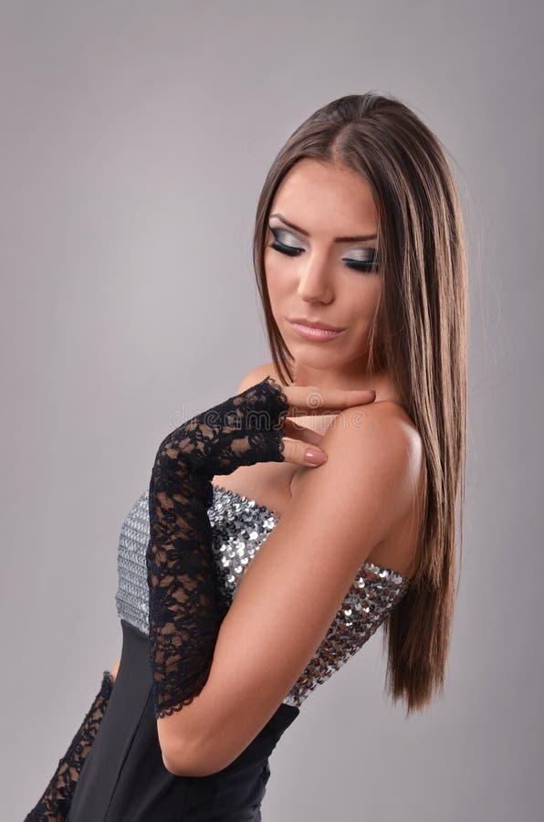 Brune magnifique avec la main sur son épaule, regardant vers le bas images stock