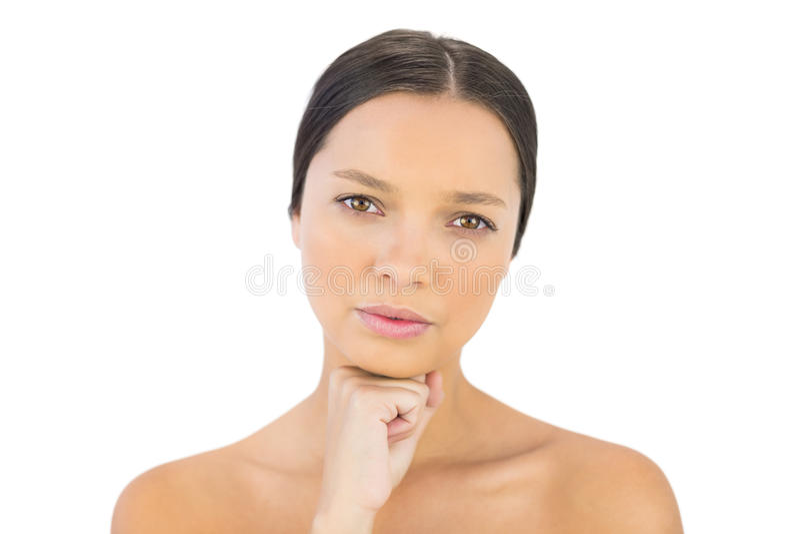 Brune magnifique sérieuse avec la main sous la pose de menton photos stock