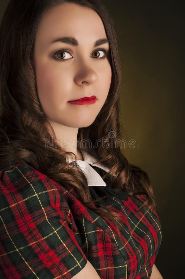 Brune mignonne dans la robe de tartan avec les lèvres et les curles rouges Portrait de studio images stock