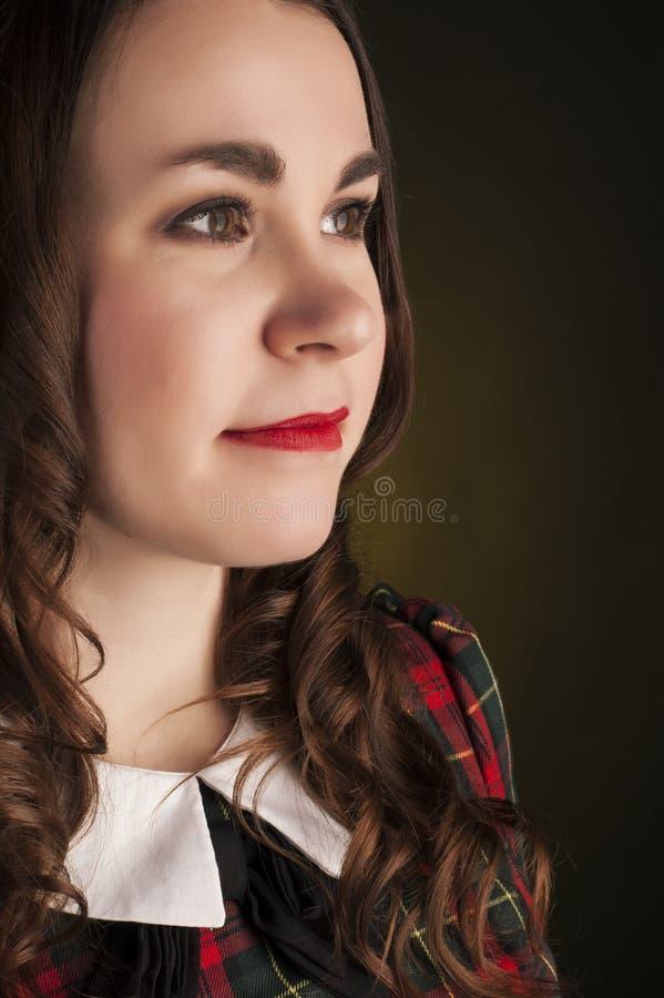 Brune mignonne dans la robe de tartan avec les lèvres et les curles rouges Portrait de studio photos libres de droits