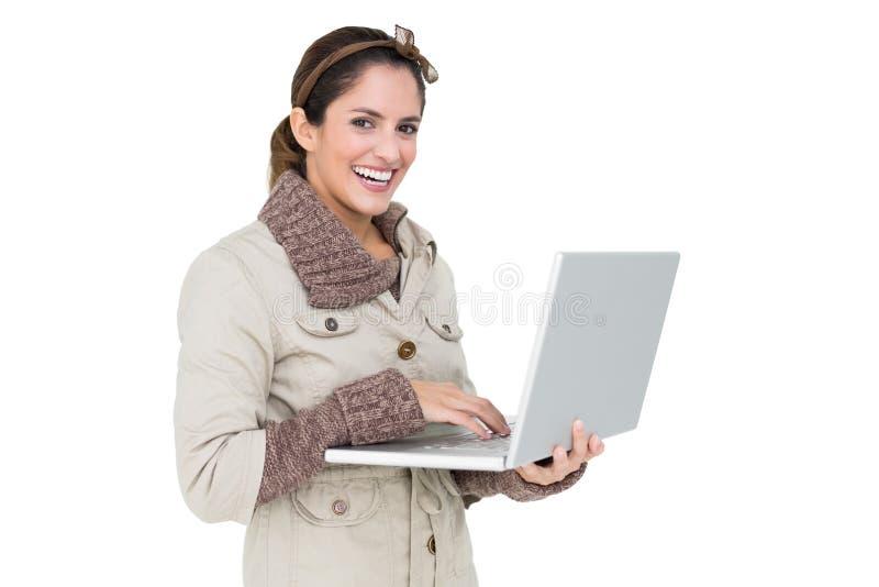 Brune mignonne heureuse de mode d'hiver tenant l'ordinateur portable images stock
