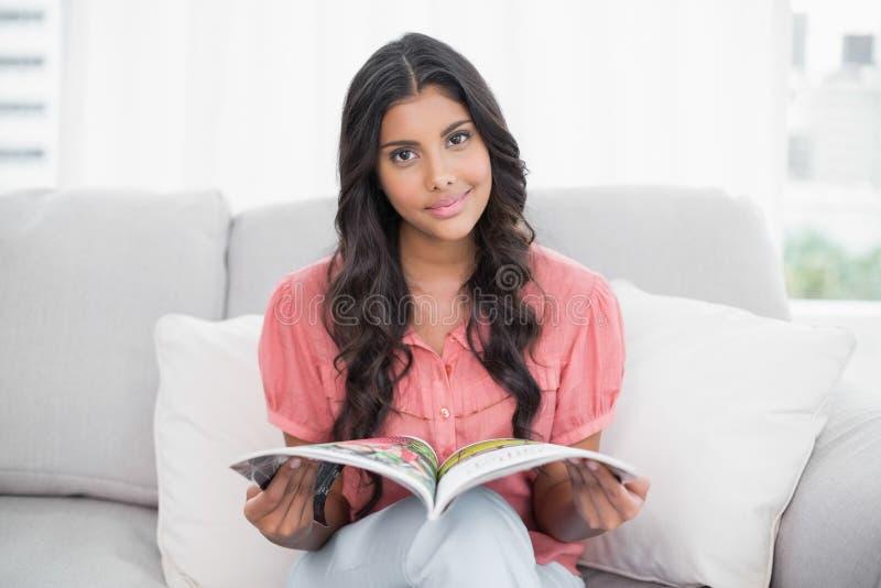 Brune mignonne heureuse se reposant sur le divan tenant la magazine photographie stock libre de droits