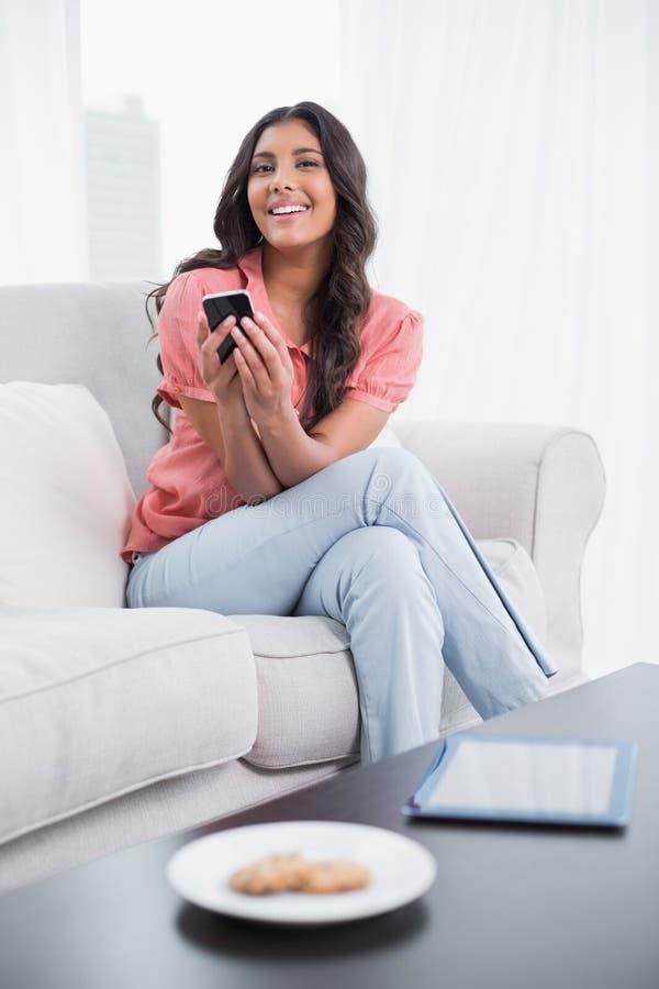 Brune mignonne heureuse se reposant sur le divan utilisant le smartphone photographie stock
