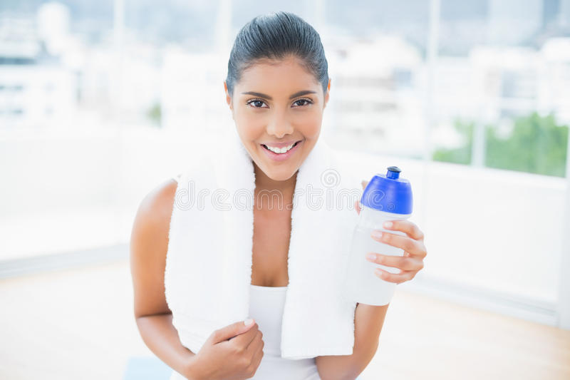 Brune modifiée la tonalité de sourire avec la serviette tenant la bouteille de sports images libres de droits