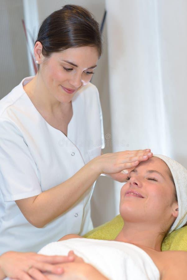 Brune obtenant le traitement principal de station thermale de massage photos libres de droits