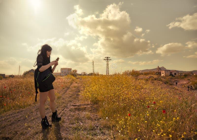 Brune perdue isolée observant son téléphone dans la campagne image libre de droits