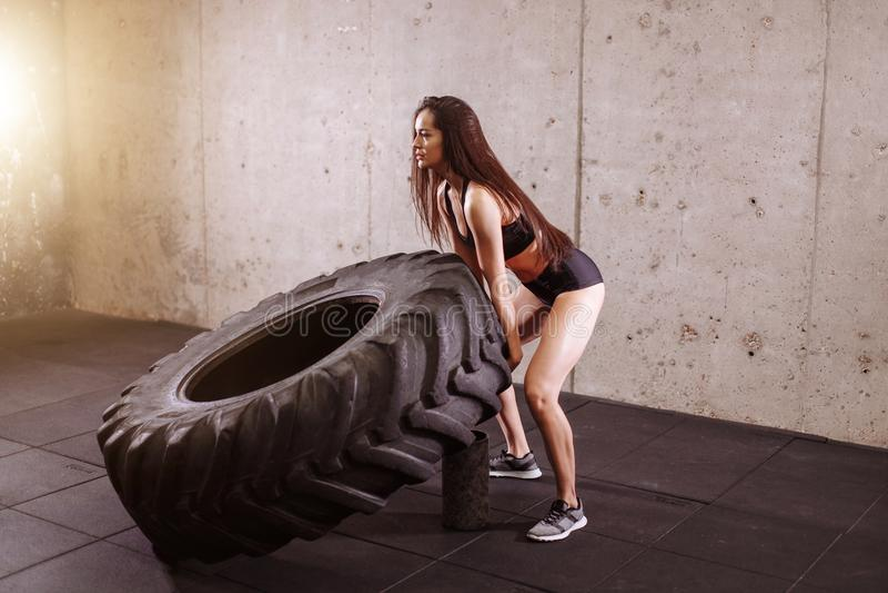 Brune renversant le grand pneu dans le gymnase photographie stock libre de droits
