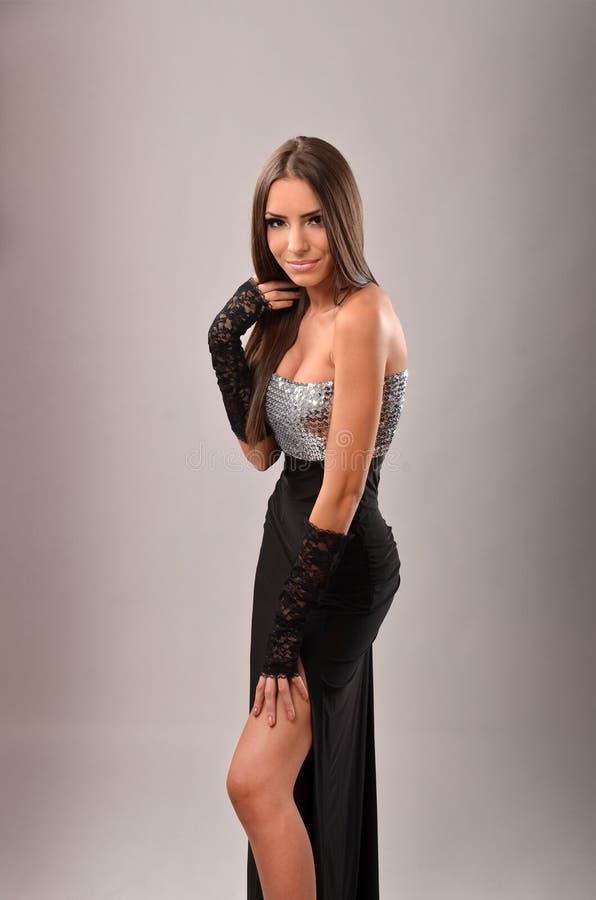 Brune sexy dans la robe de soirée indiquant sa jambe photographie stock