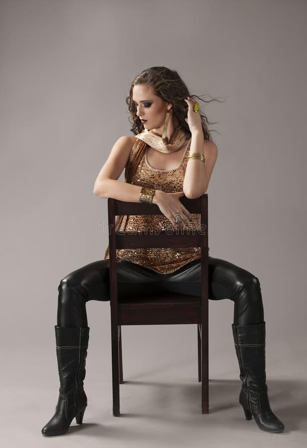 Brune sexy dans le noir et l'équipement grunge d'or, posés sur la chaise noire photographie stock libre de droits