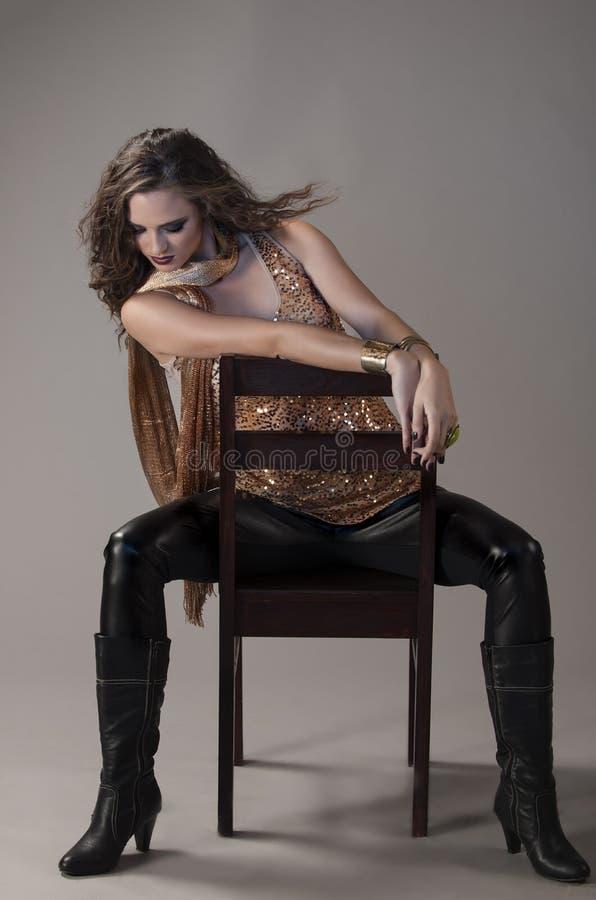 Brune sexy dans le noir et l'équipement grunge d'or, posés sur la chaise noire image libre de droits