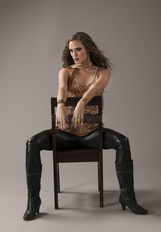 Brune sexy dans le noir et or posé sur la chaise noire image libre de droits
