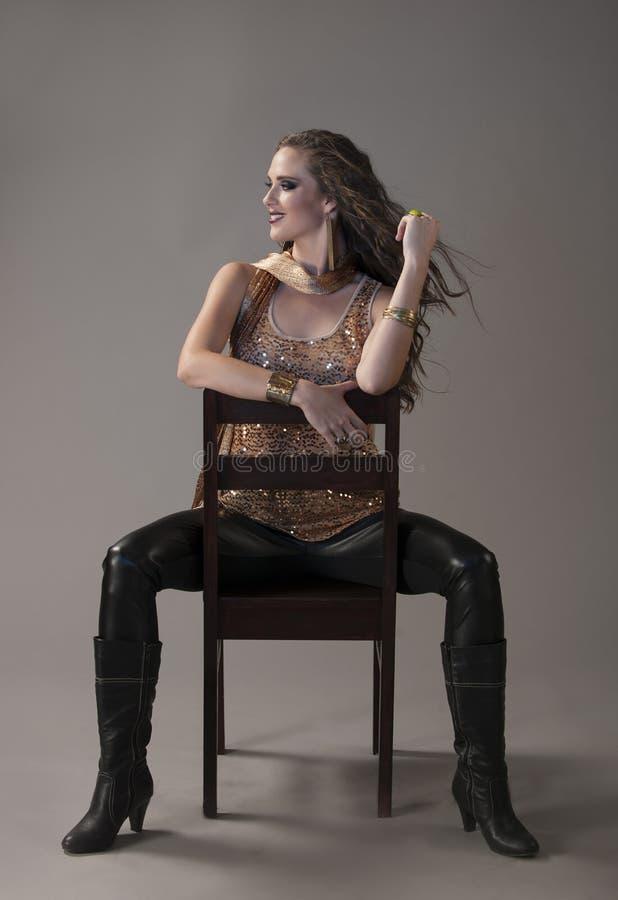Brune sexy dans le noir et or posé sur la chaise noire photographie stock libre de droits