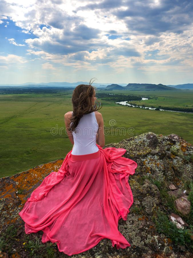 Brune sexy dans une belle robe au bord d'une falaise photographie stock