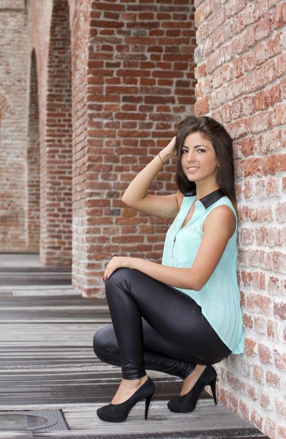Brune sexy se penchant contre un mur photos stock