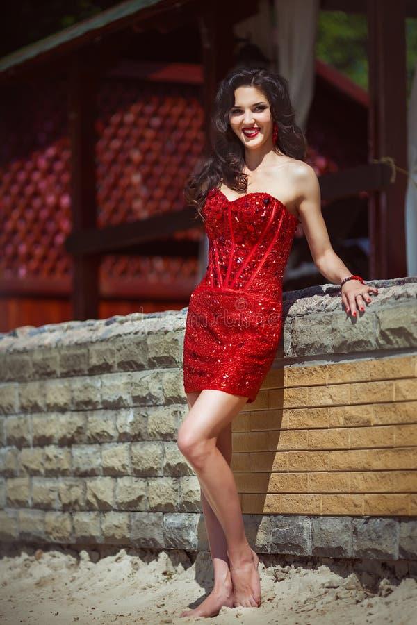 Brune sinueuse fascinante dans la robe en pierre rouge avec le corps sexy photos libres de droits