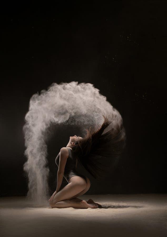 Brune sur ses genoux en nuage de poussière blanc photo libre de droits