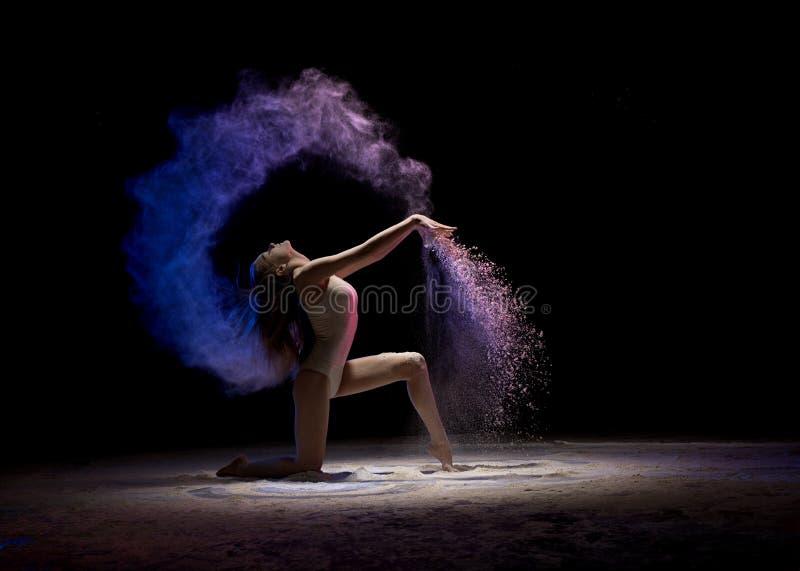 Brune sur ses genoux en poussière de couleur dans l'obscurité images stock
