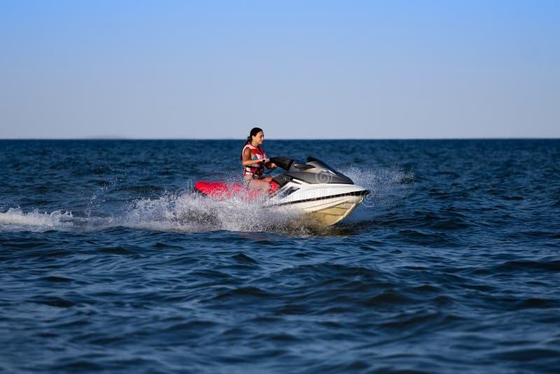 Brune sur un scooter de mer photographie stock libre de droits