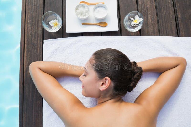 Brune tranquille se trouvant sur le poolside de serviette avec des traitements de beauté images libres de droits