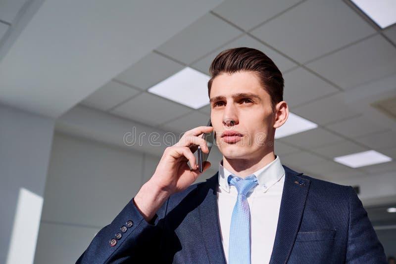 Brunet biznesmen opowiada na telefonie w biznesowym biurze zdjęcie royalty free