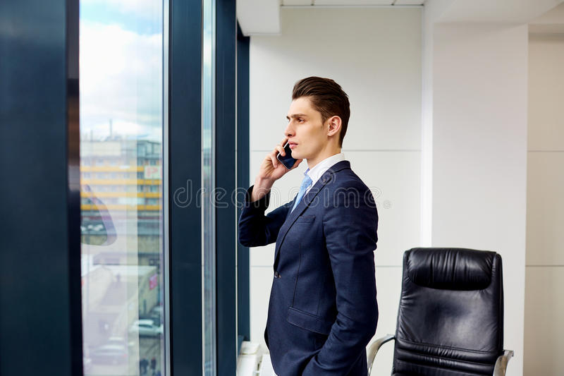 Brunet biznesmen opowiada na telefonie w biznesowym biurze obraz royalty free