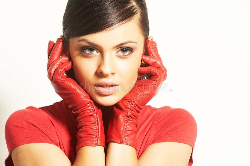 Brunet d'Atractive dans le chemisier rouge et les gants rouges photo stock