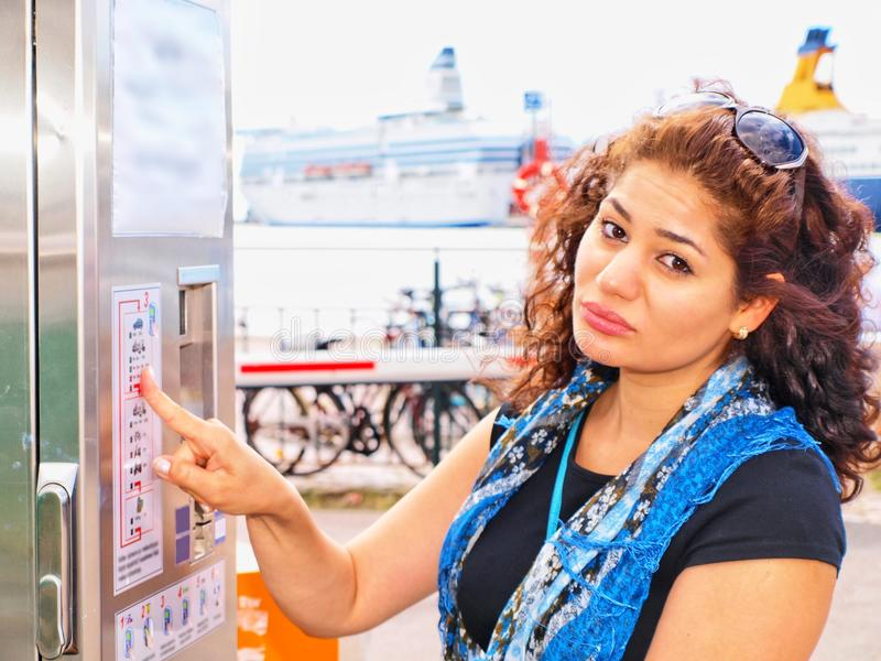 Brunet infeliz na máquina de vending do bilhete fotografia de stock royalty free