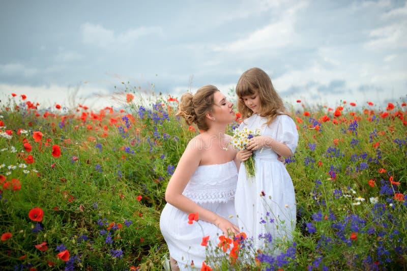 Brunet matka z śliczną młodą córką na makowym polu z wh fotografia stock
